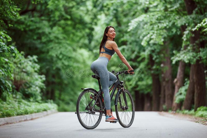 Looking behind. Female cyclist on a bike on asphalt road in the forest at daytime stock photos