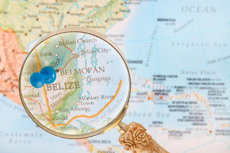 Looking in on Belmopan, Belize. Blue tack on map of Central America with magnifying glass looking in on Belmopan, Belize royalty free stock photography