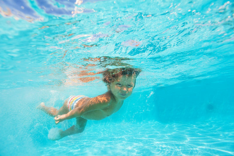 Looking boy moving while swimming undewater. Looking boy moving while swimming under the clear blue water of swimming pool stock photo