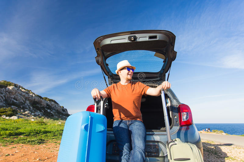 Looking at camera, a cheerful man going away for the weekend by the car with luggage.  royalty free stock photos