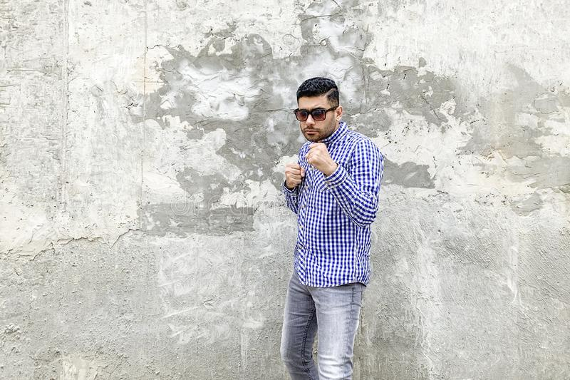 Looking at camera with serious face and ready to punching in boxing pose. Portrait of angry handsome bearded young man in checkered blue shirt and sunglasses royalty free stock photos
