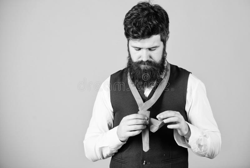 Looking classy. Elegant man. Bearded man tying a tie. Brutal caucasian man adjusting fashion accessory. Man with long. Beard and moustache dressing in classic royalty free stock photography