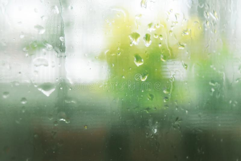 Looking through the clear glass to the outside while it rain. See dew drops, moisturizer and cool refreshing and empty space for text stock photography