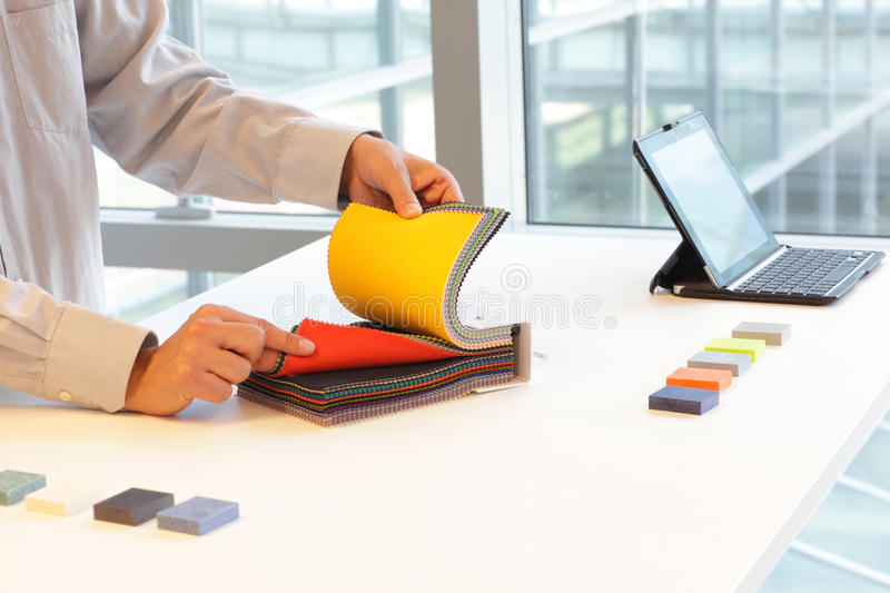 Looking at color swatches. Male hands looking through color fabric swatches on desk with colored tiles and laptop next to large windows stock image
