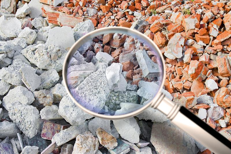 Looking for danger asbestos particles in industrial waste after demolishing a concrete wall - Concept image seen through a. Magnifying glass royalty free stock photography
