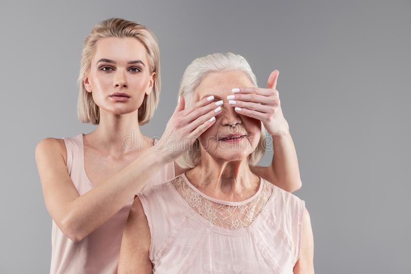 Serious short-haired blonde girl closing eyes of her senior mother royalty free stock photos