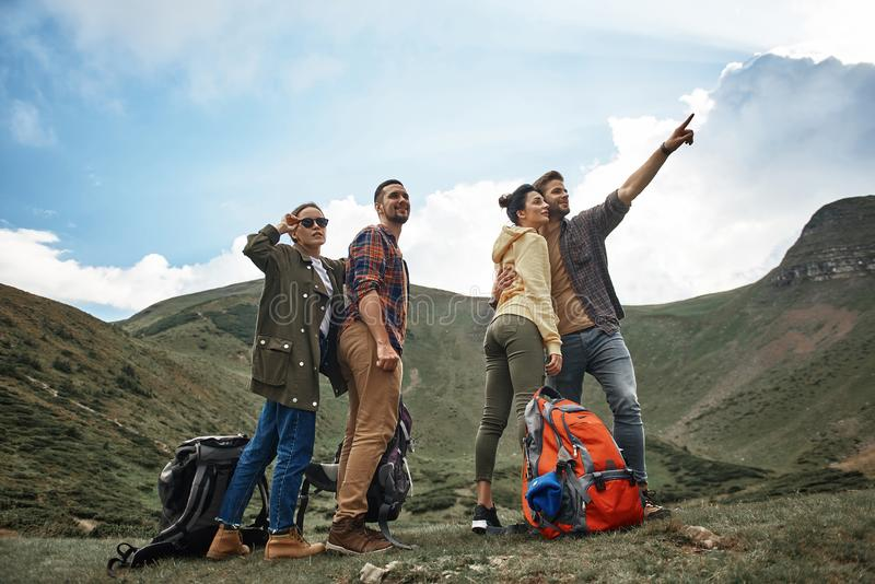 Two couples feeling interested and looking at the landscape. Looking into the distance. Active young hikers putting their backpacks off ad thoughtfully looking stock photo
