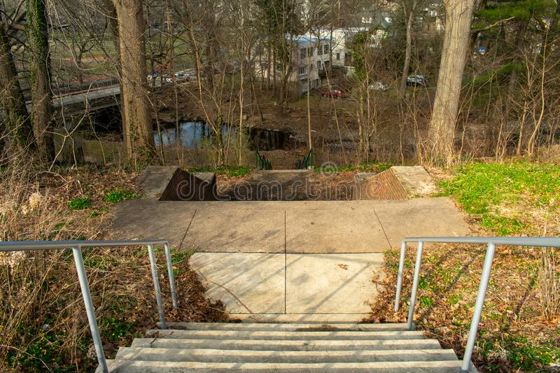Looking Down a Concrete Stairwell. With Fences on Each Side in a Suburban Neighborhood royalty free stock image