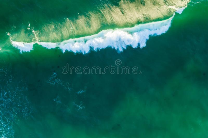 Looking down at crushing green ocean wave at sunset. stock photography
