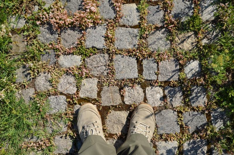 Pair of feet in canvas shoes on cobble stones sidewalk royalty free stock photo
