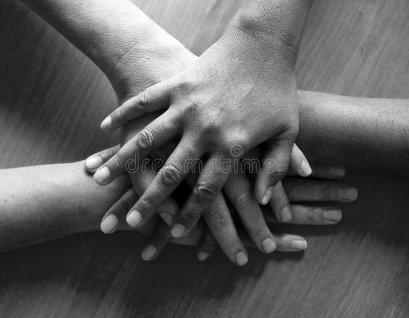 Looking down on four hands placed ontop of each other, the top h royalty free stock photos