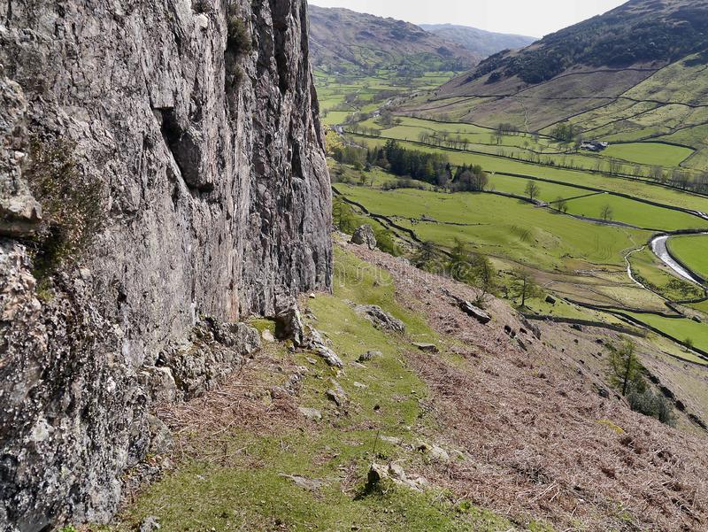 View down Great Langdale from rockface on hillside. Looking down the Great Langdale valley, Lake District, by rockface on minor grassy path stock image