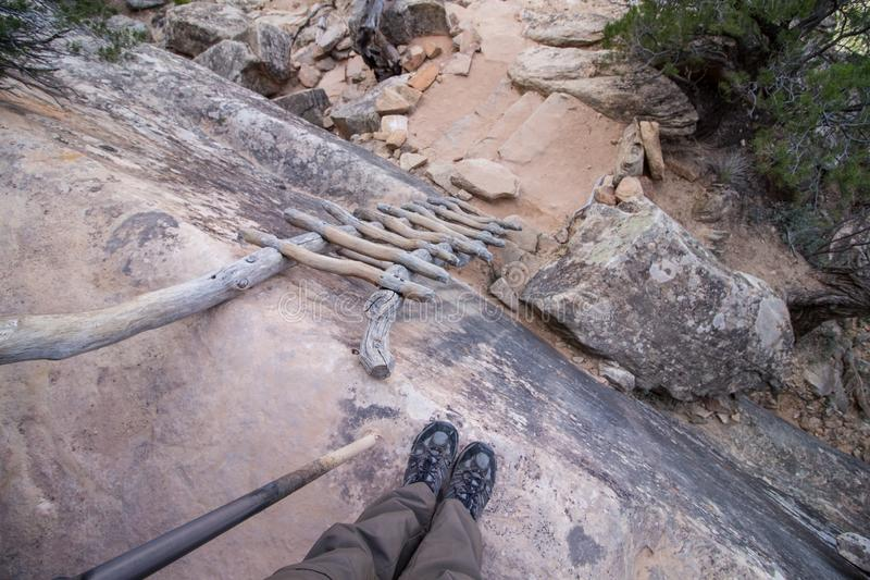 Looking down an old wooden ladder leaning against a rocky cliff, first person perspective. royalty free stock image