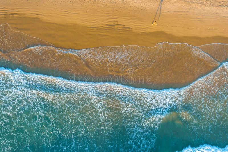 Looking down at one person running on ocean beach. royalty free stock image