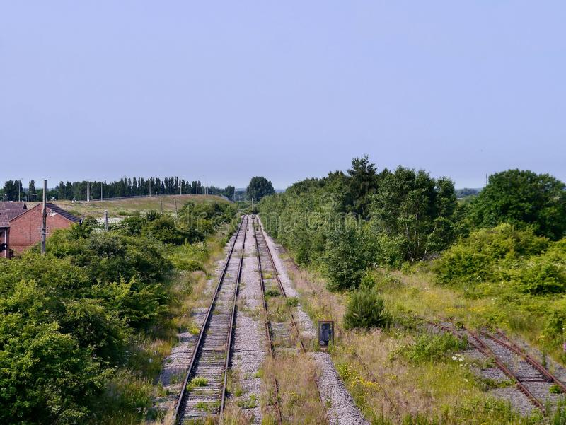 Looking down redundant railway lines. Redundant railway lines with heavy surrounding foliage, viewed from above stock photo