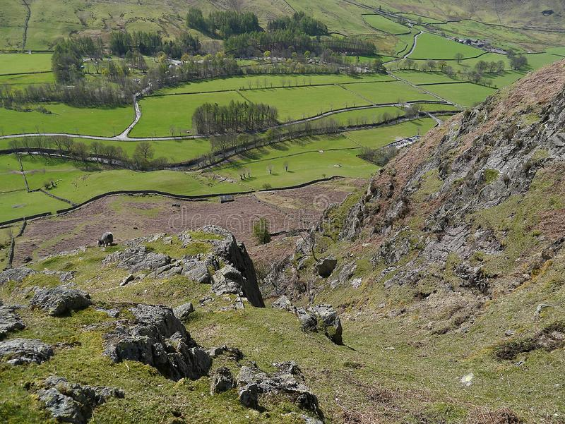 Looking down rocky hillside to Great Langdale valley. Looking down from a rocky hille to verdant fields in Great Langdale valley, Lake District stock image