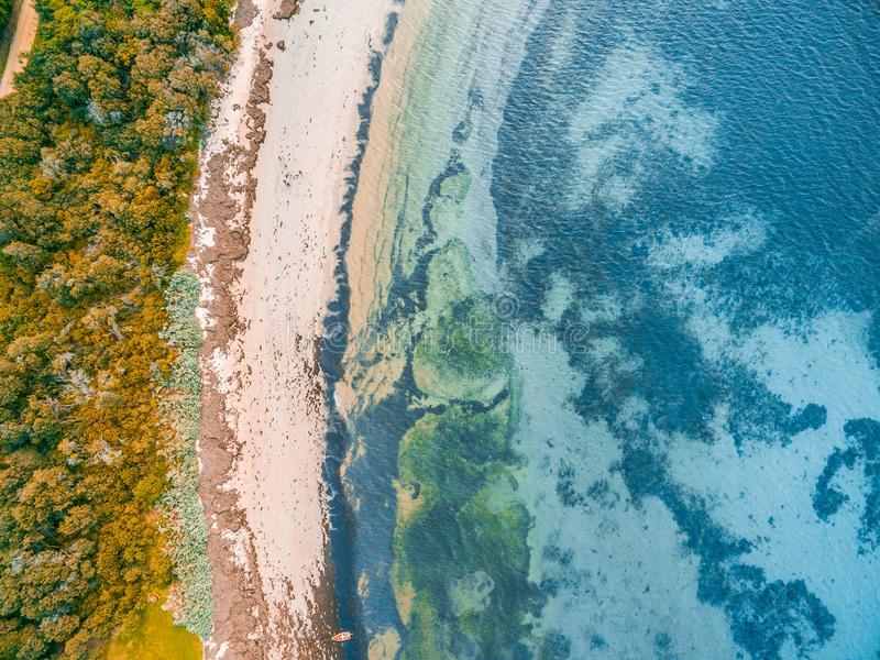 Shallow ocean water and rocky beach. Looking down at shallow ocean water and rocky beach stock photography
