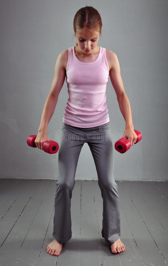 Looking down teenage sportive girl is doing exercises to develop muscles isolated on grey background. Sport healthy lifestyle royalty free stock images