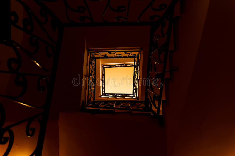 Looking down a three story staircase. Looking up a three story staircase in ancient building stock photography
