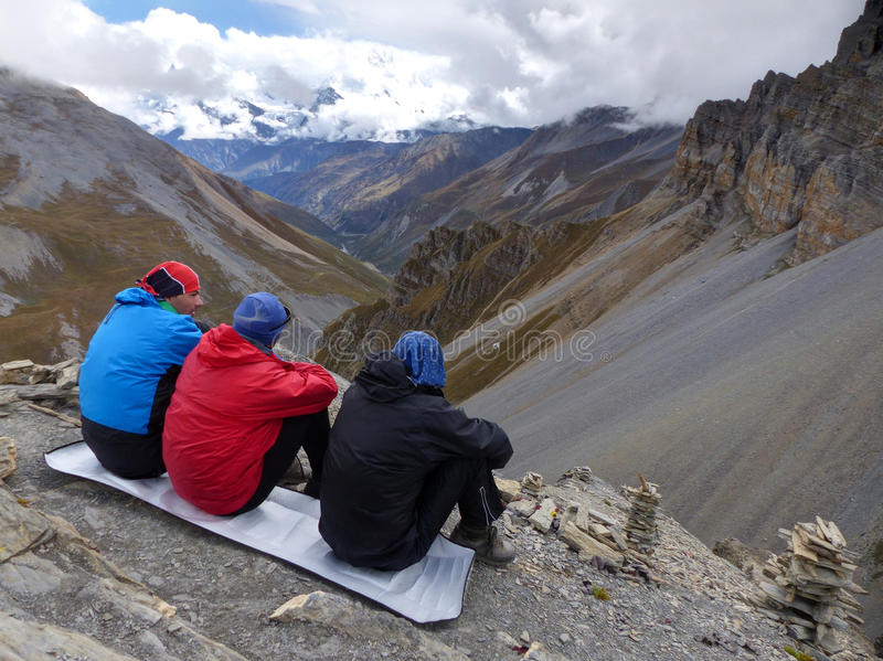 Looking down to the valley. Tourists looking to the Annapurna Mountain Range from Thorong High Camp - Annapurna Circuit Trek in Nepal stock image
