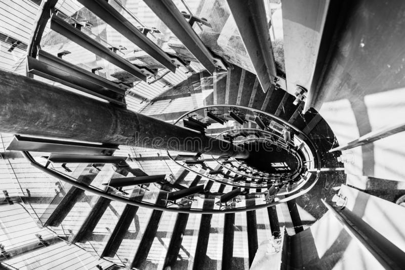 Looking down from the top of a circular staircase; bright light passing through the glass panels of the railing and creating. Shadows and shapes on the stairs royalty free stock image