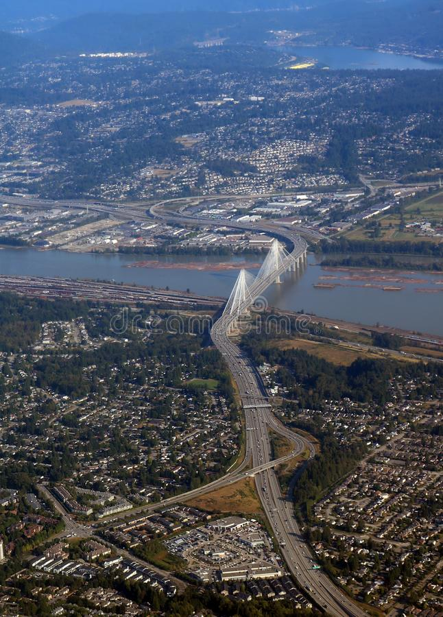Arial view of long bridge over Fraser River and city of Vancouver from window of passenger commercial jet. Looking down on Trans Canada Highway One and the Port royalty free stock image