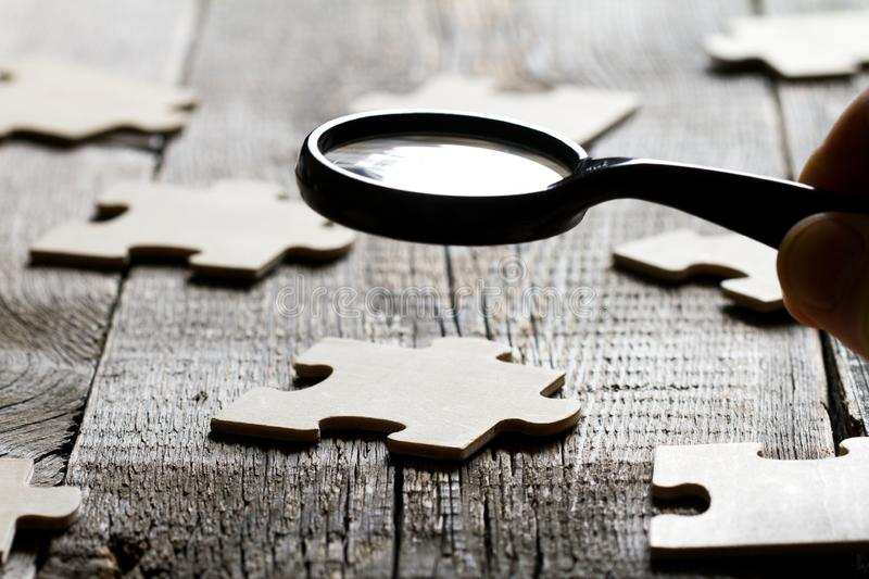 Looking for an employee partner in business concept with puzzle and magnifier stock photo