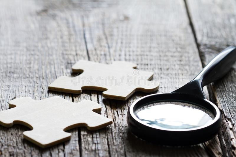 Looking for an employee partner in business concept with puzzle and magnifier. Abstract stock images