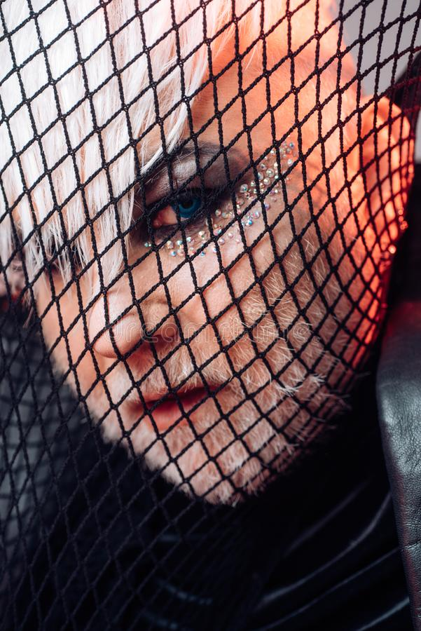 Looking at fashion at unique way. Heterosexual man with male makeup. Transgender man cover face with fishnet. Male. Makeup look. Fetish fashion. BDSM fashion royalty free stock image