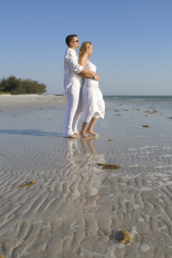 Looking for the future. Man and a woman standing on a beach. Both wearing white clothes stock photos