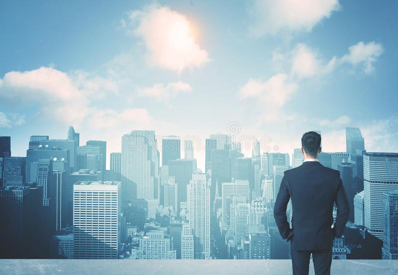 Looking at future city. Businessman standing on a roof and looking at future city stock images