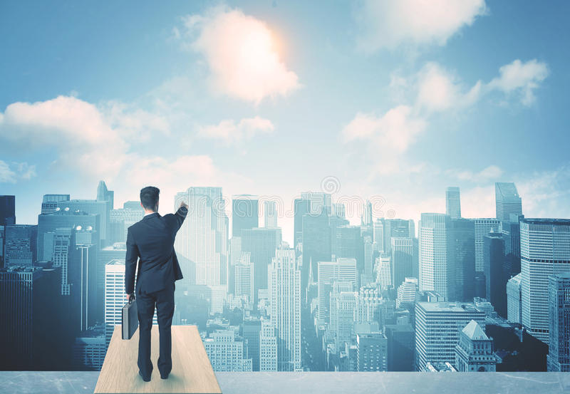 Looking at future city. Businessman standing on a roof and looking at future city stock photos