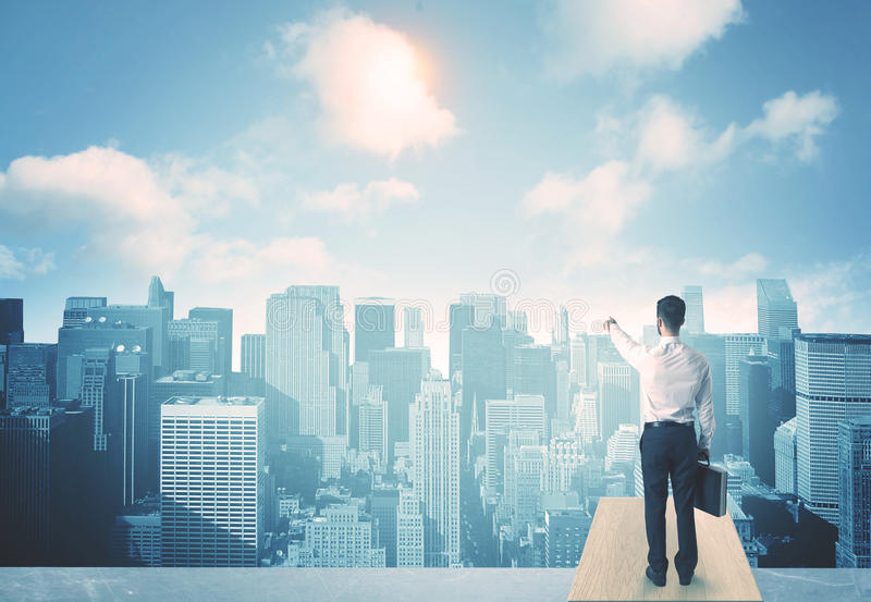 Looking at future city. Businessman standing on a roof and looking at future city royalty free stock image