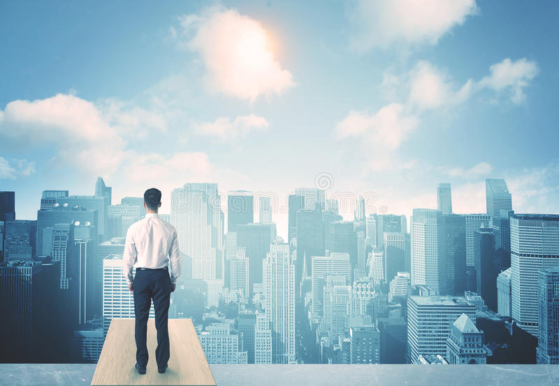 Looking at future city. Businessman standing on a roof and looking at future city stock photo