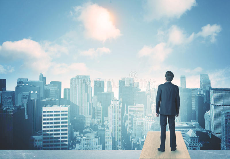 Looking at future city. Businessman standing on a roof and looking at future city royalty free stock photography