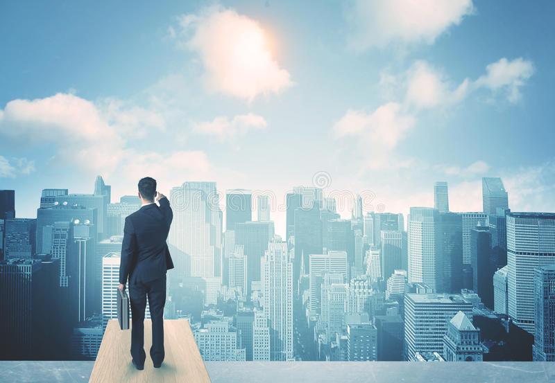 Looking at future city. Businessman standing on a roof and looking at future city stock photography