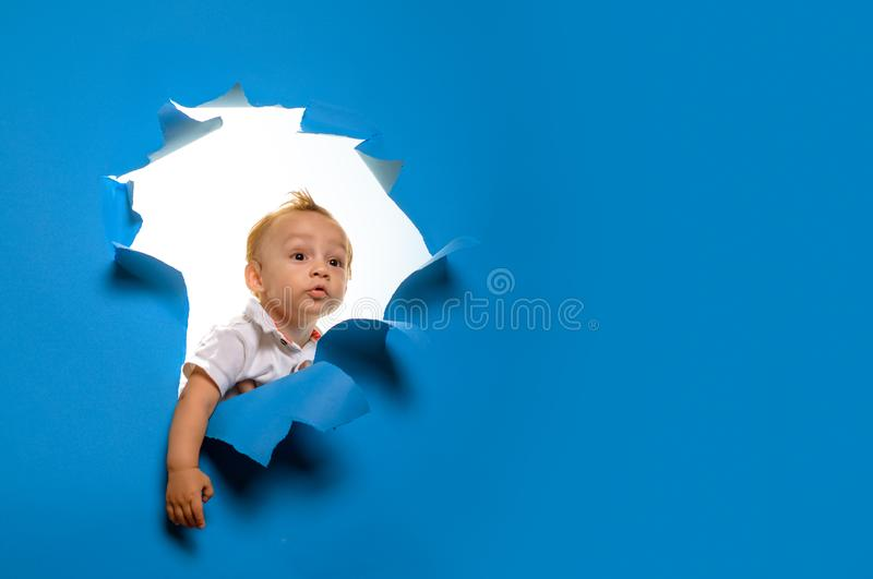 Looking in future. Curious boy child look out of hole in paper. Entrance to new life beginning. Little child peek royalty free stock images