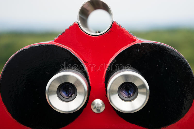 Looking for Future Opportunities. Red-colored binoculars at a coin-operated lookout observation point looking off into the distance stock images