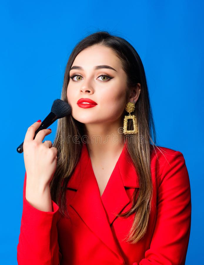 Looking good and feeling confident. Gorgeous lady makeup red lips. Attractive woman applying makeup brush. Hiding all royalty free stock photography