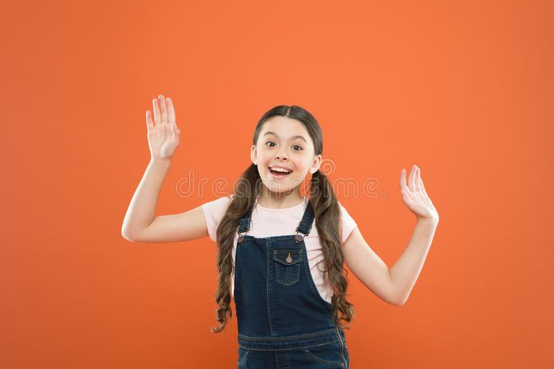 Looking happy and excited. Happy little girl with cute smile on orange background. Cheerful small child happy smiling. With fashion look. Adorable kid enjoying stock images