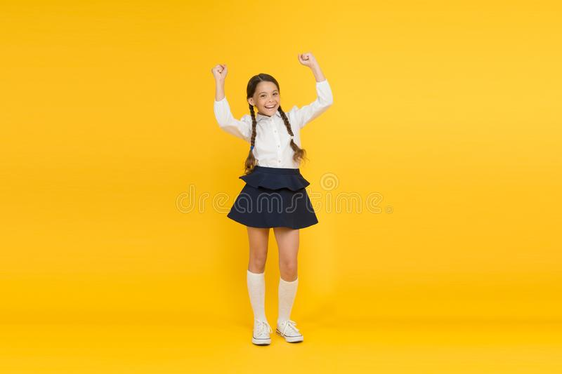 Looking happy and excited. Happy little girl with cute smile on orange background. Cheerful small child smiling in stock images