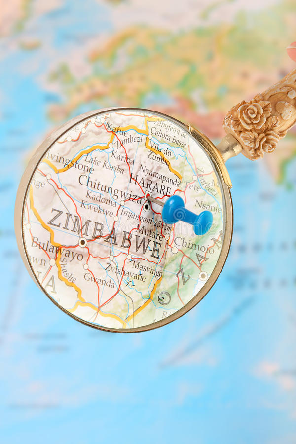 Looking in on Harare, Zimbabwe, Africa. Blue tack on map of Africa with magnifying glass looking in on Harare, Zimbabwe royalty free stock photos