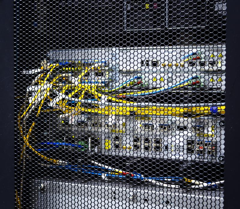 Looking through honeycomb pattern doors inside modern big data server rack in data center with network servers hardware and stock photos