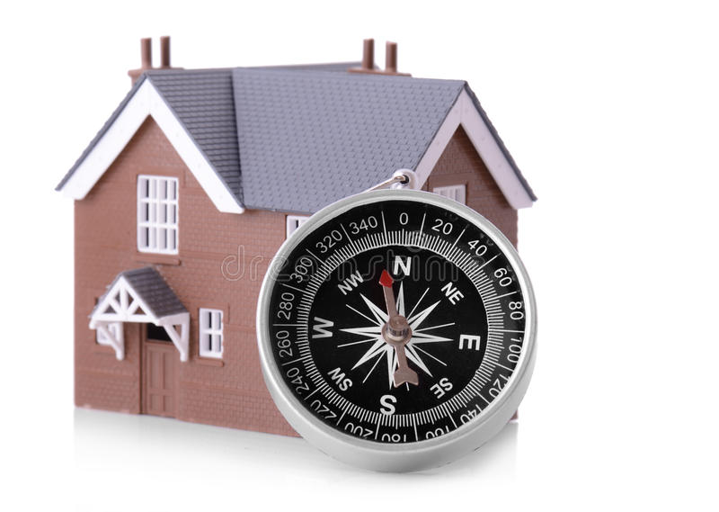 Looking for a house. Concept of looking for a house, a compass with small house isolated on a whits background royalty free stock image