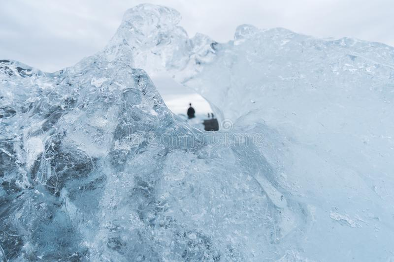 Looking Through an Iceberg at Tourists in Iceland stock images