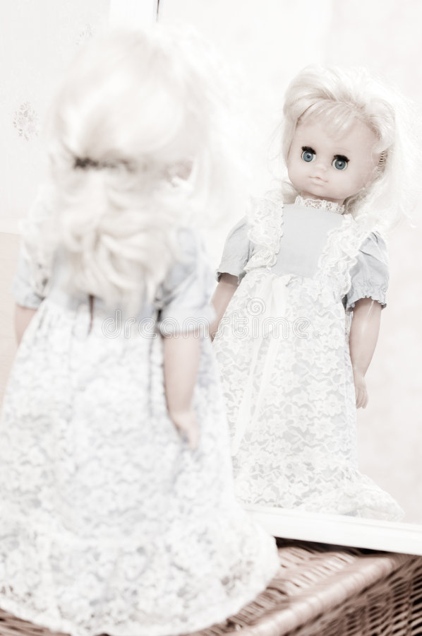 Looking for identity - vintage doll at the mirror stock images