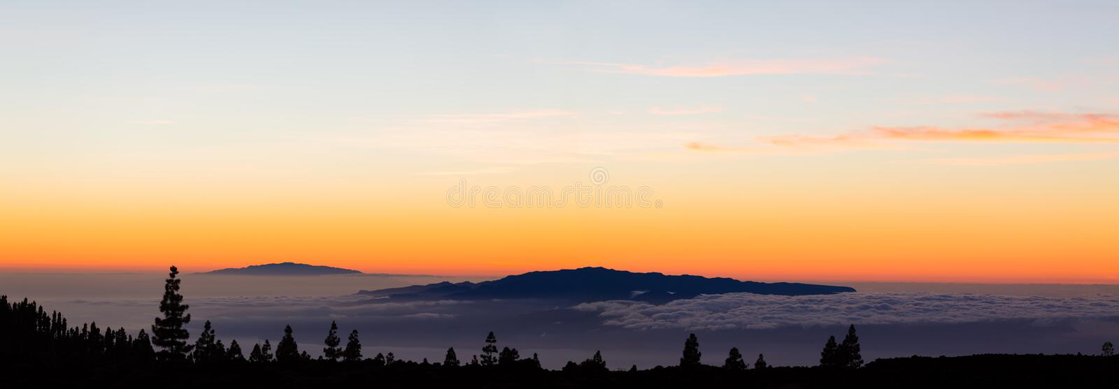 Looking at inspirational landscape ocean view. Beautiful sunset from Tenerife island. Panoramic view with mountains on islands and clouds over ocean and sunset royalty free stock photo