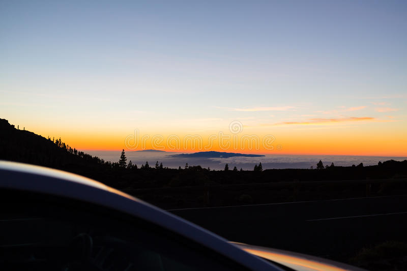 Looking at inspirational landscape ocean view. Car driver or passenger on road trip looking at beautiful sunset sky on Tenerfie Canary Islands, Spain stock photography