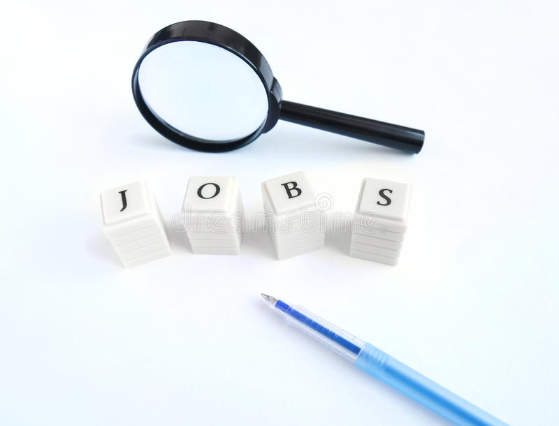 Looking for a job. A concept photograph of a magnifier and pen with the word jobs spelt out with blocks royalty free stock photos