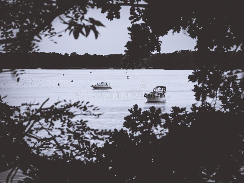 Looking through a leaf hole on a calm lake with boats royalty free stock photography
